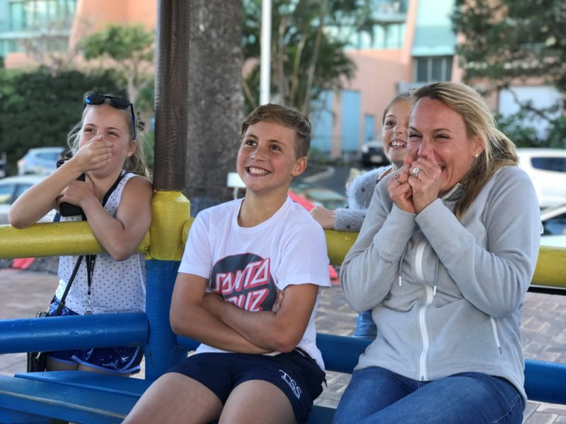 A family watching the video of their ride on the Sling Shot at their seated video area.