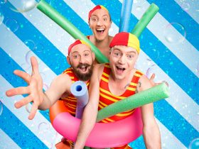 Three men pose in red and yellow swimsuits with pool toys
