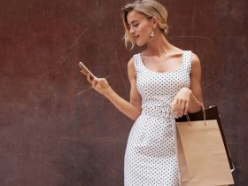 A fashionable woman is holding a mobile phone, looking at the screen and holding shopping bags