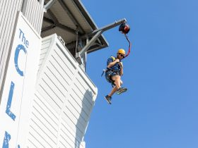 Instructor jumping off the top of the abseiling tower