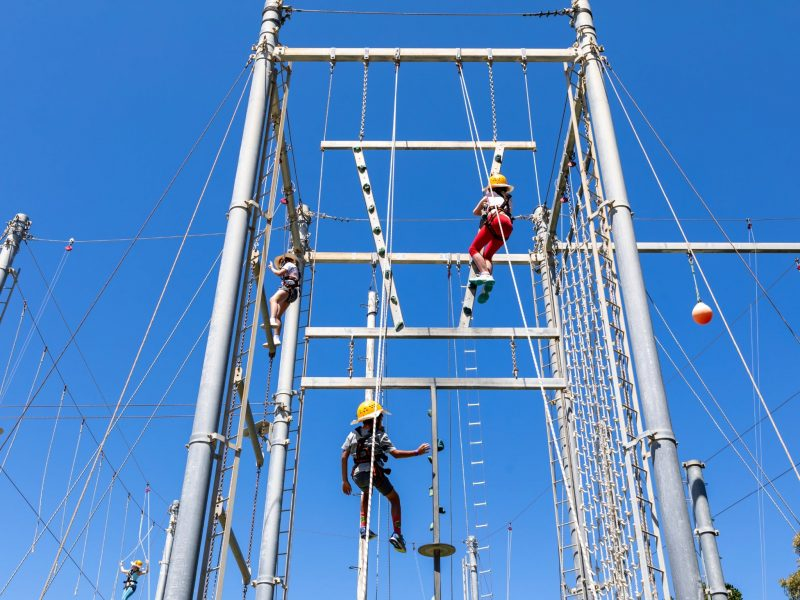 Teenagers climbing a series of high ropes, ladders and poles