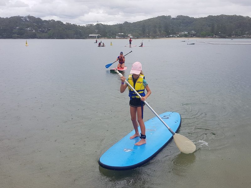 Instructor and little girl learning to stand up paddle board on Tallebudgera Creek