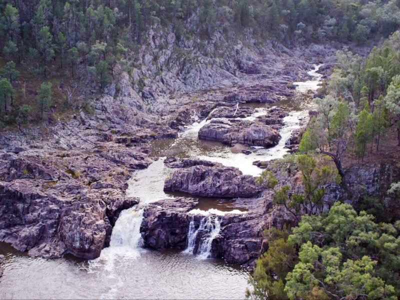River and small falls in rocky ravine.