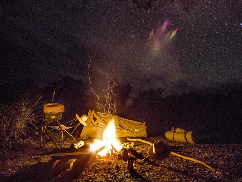Campfire and camp at night.