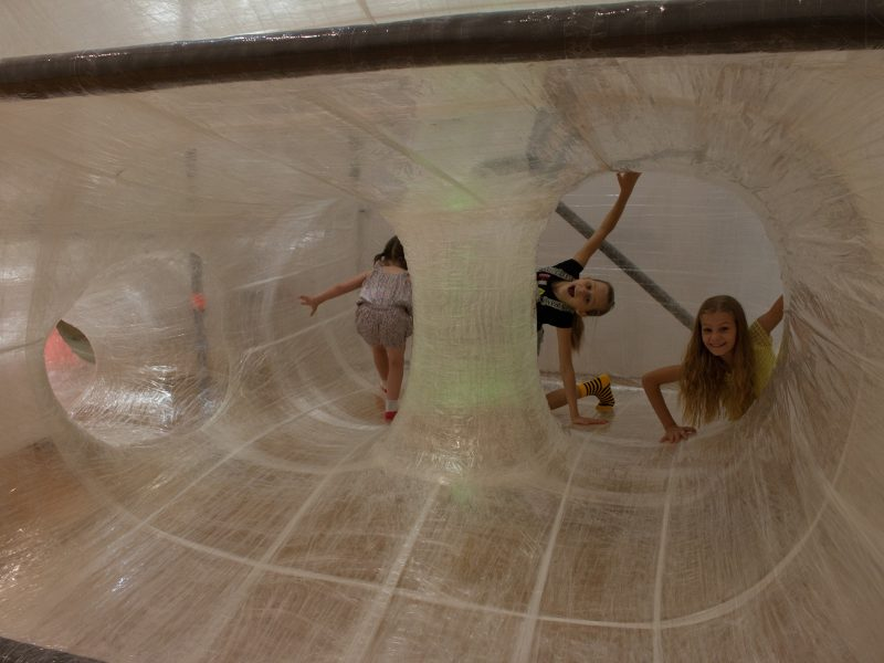 Several children explore the internal tunnels and slides of the TapeScape