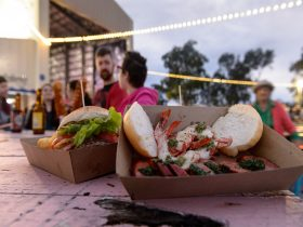 Burgers on table in front of couple at Riverfeast