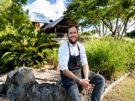 Chef sits on rocks in front of garden at Eleven Acres Restaurant