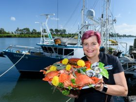 Lady holding seafood platter in front of of fishing boat on Burnett River