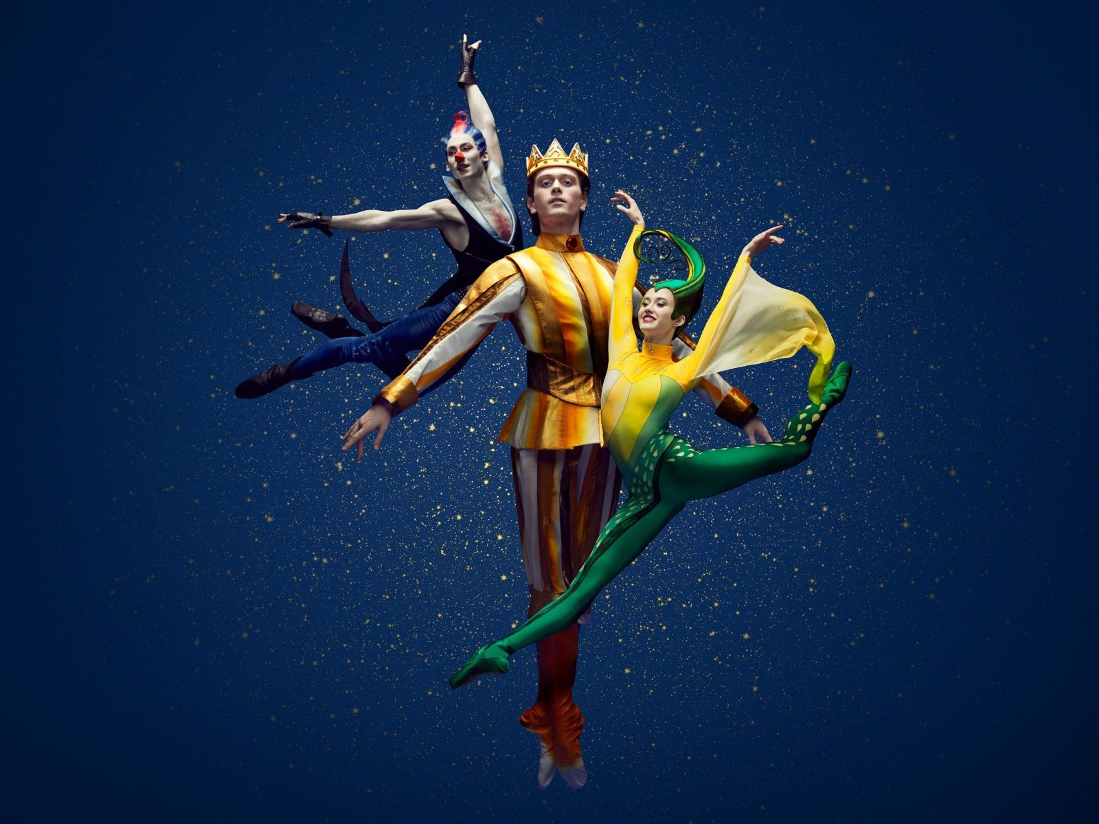 Three people are suspended in balletic poses - one standing tall dressed as a yellow prince.