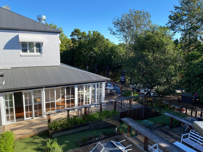 Photo of the exterior of The Glasshouse showing deck area and indoor dining area