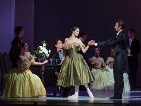 Female ballet dancer holding male ballet dancer hand