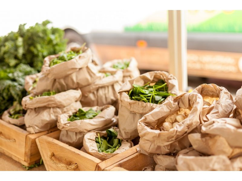 Bags of fresh spinach and mushrooms on display at a market stall