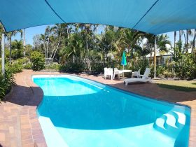 Pool with shade sail and outdoor seating