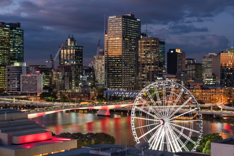 Wheel of Brisbane aerial shot looking out over the Wheel of Brisbane lit up at night time.