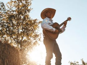 Tom Curtain singing with guitar with sun and tree on background
