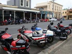 Vintage Japanese motorcycles on tour in country town