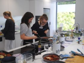 Chloe cooking with a workshop participant