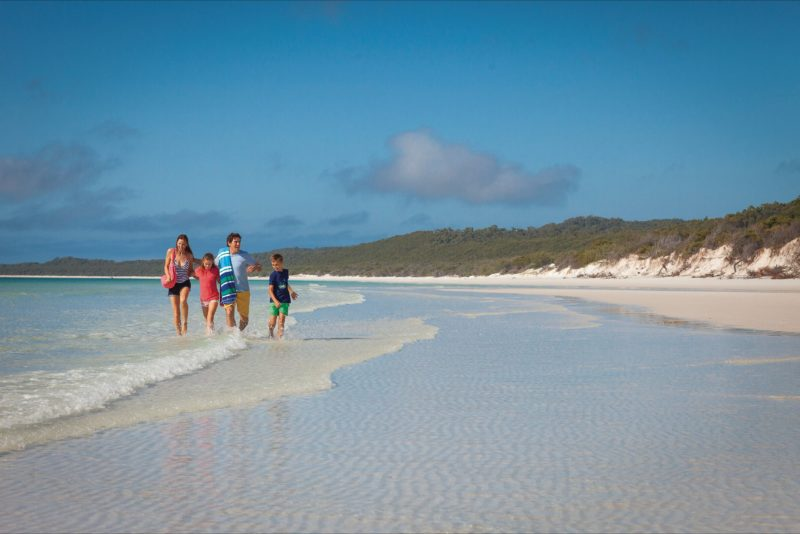 Young family on water's edge at Whitehaven Beach.