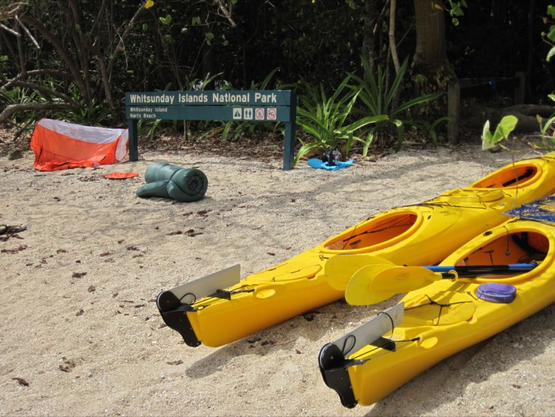Sea kayaks on the beach near tents.