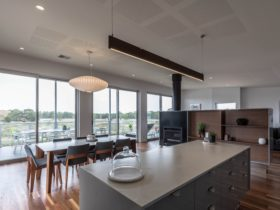open plan living, kitchen and dining area over looking the balcony and outdoor dining