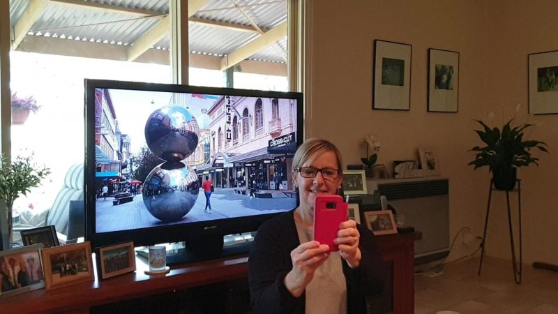 A woman takes a selfie in front of the television during the home tour A Tourist In Adelaide.