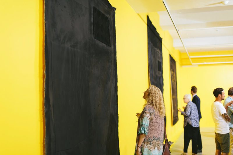 A woman holding a glass of wine looks at a black painting on a yellow wall