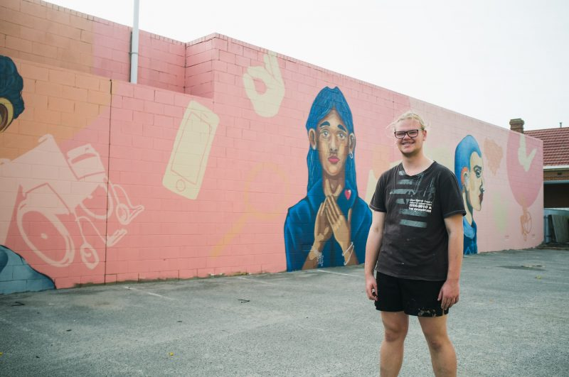Artist William Maggs standing in front of street art with colourful faces and access symbols