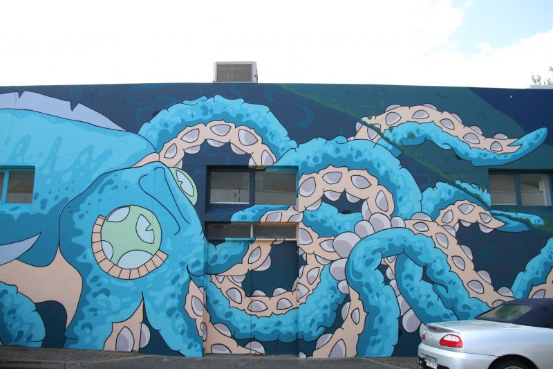 Blue octopus street art on side of building