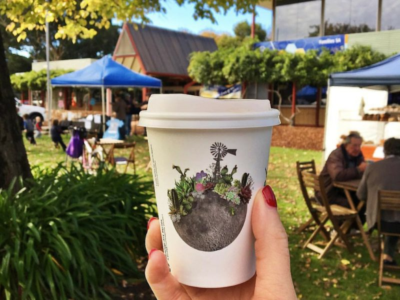 coffee cup held in front of market scene