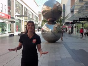 A tour guide discusses the Mall's Balls sculpture in Rundle Mall, Adelaide on a virtual tour.