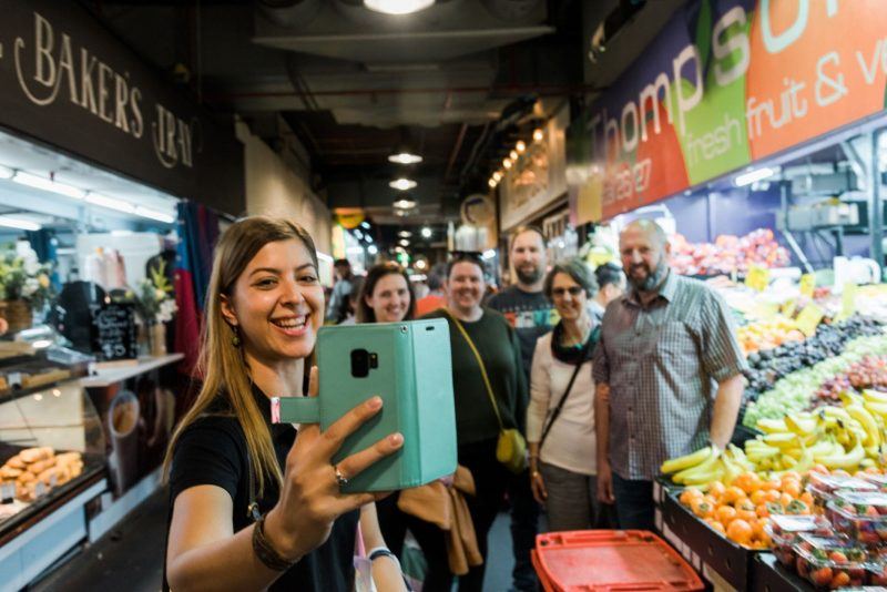 A tour guide takes a selfie with guests in the Adelaide Central Market.
