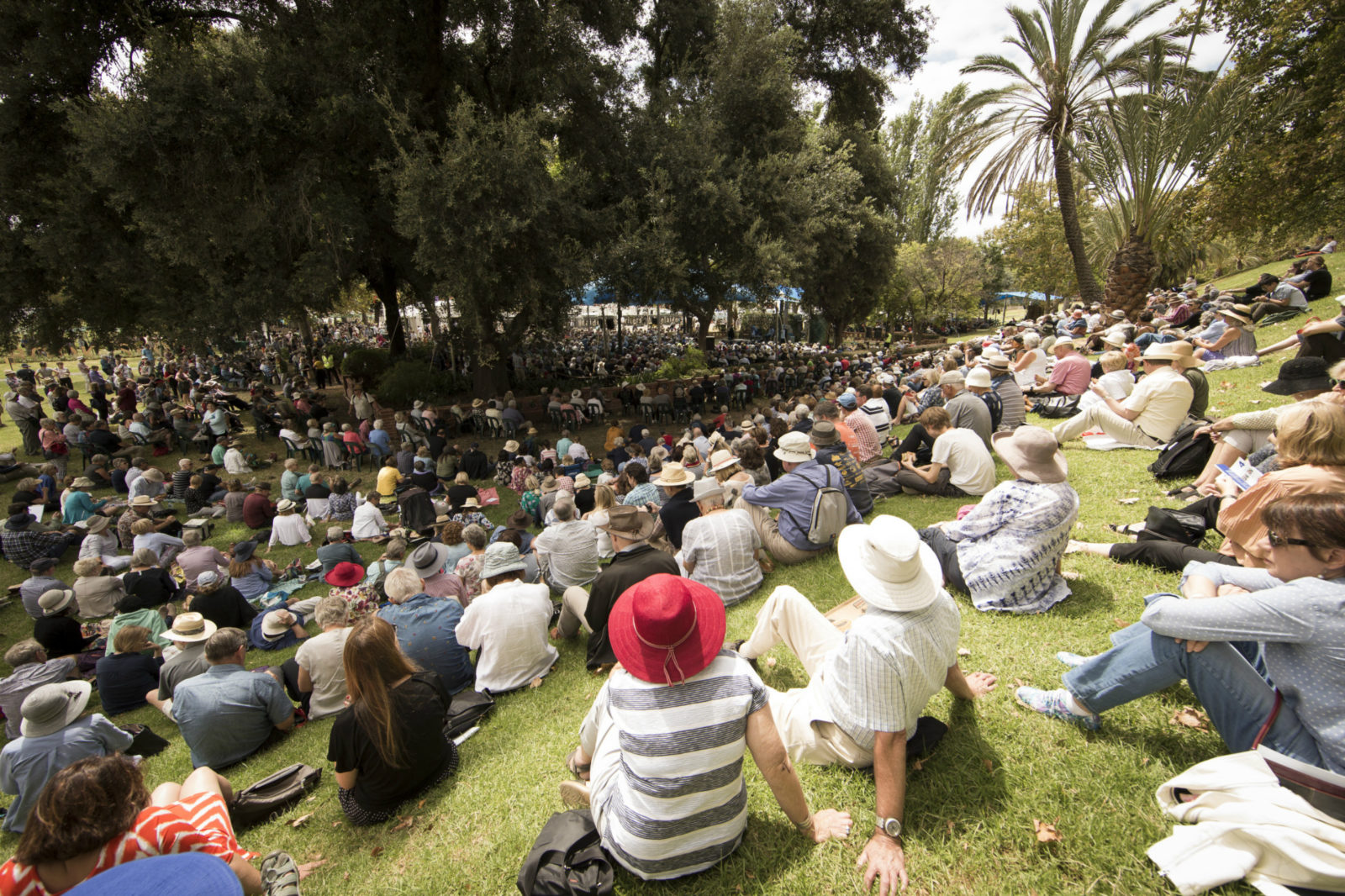 Crowds sit and gather on the grass around the West Stage