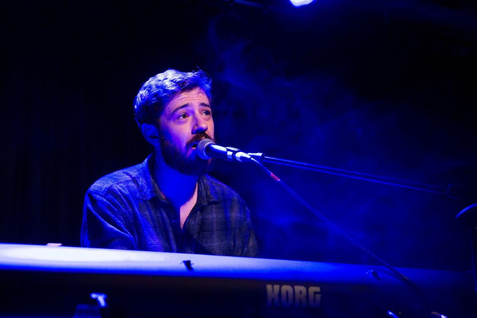 AJ Holmes sits behind keyboard on stage singing.