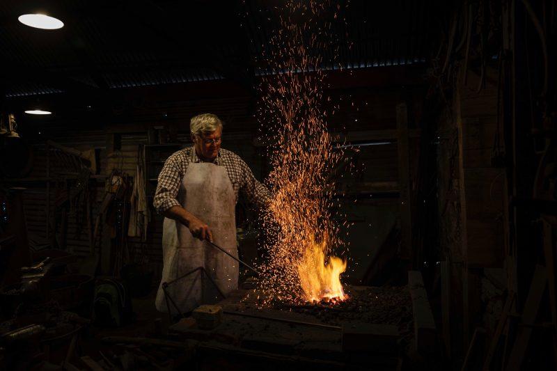 Angaston blacksmith stoking the coals