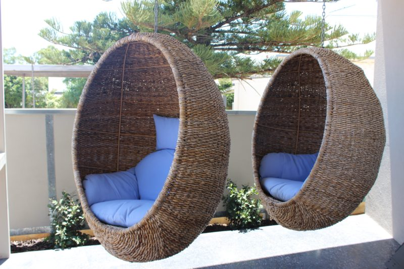 Image shows two relaxing Hanging wicker Pod chairs