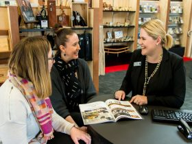 Female employee with 2 female customers sitting at desk, looking at visitor guide book and smiling