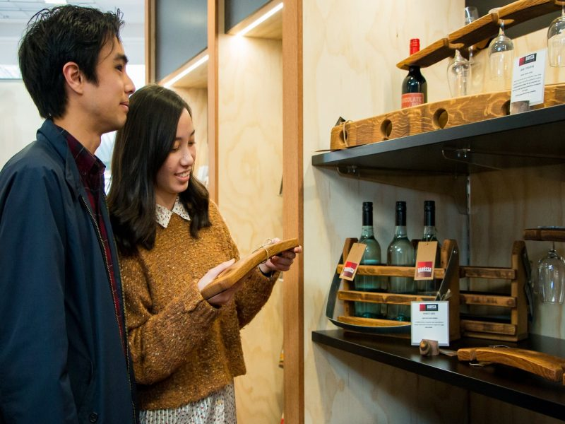Female and male couple looking at Barossa Made gifts. Female looking and smiling at product in hand