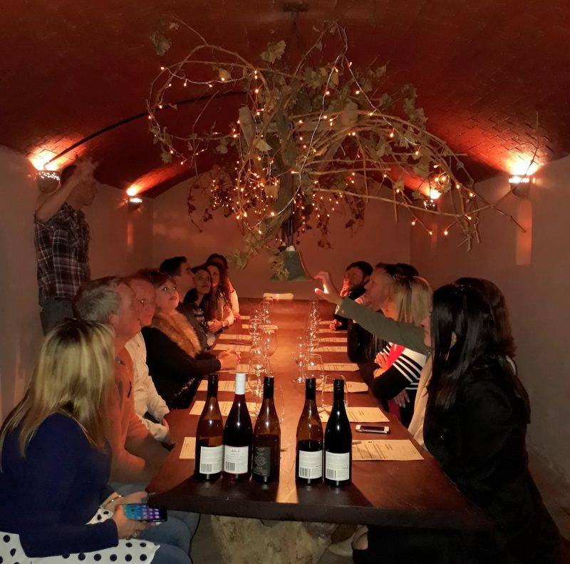 Wine tasting under ground in a softly lit room with the winemaker talking about his wines.