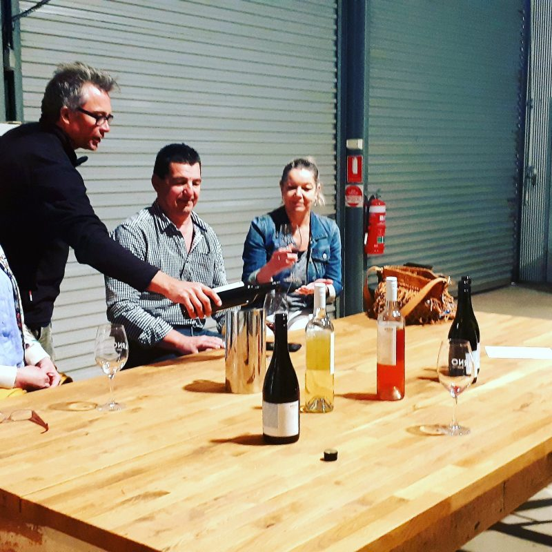 Wine maker pouring his wine to three visitors in his shed.