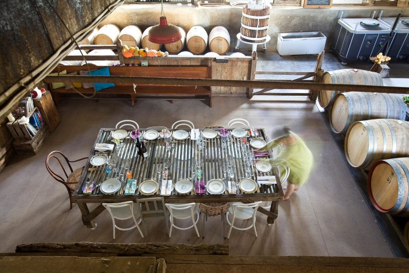 View from above wool classing table in center of winery set for dinner