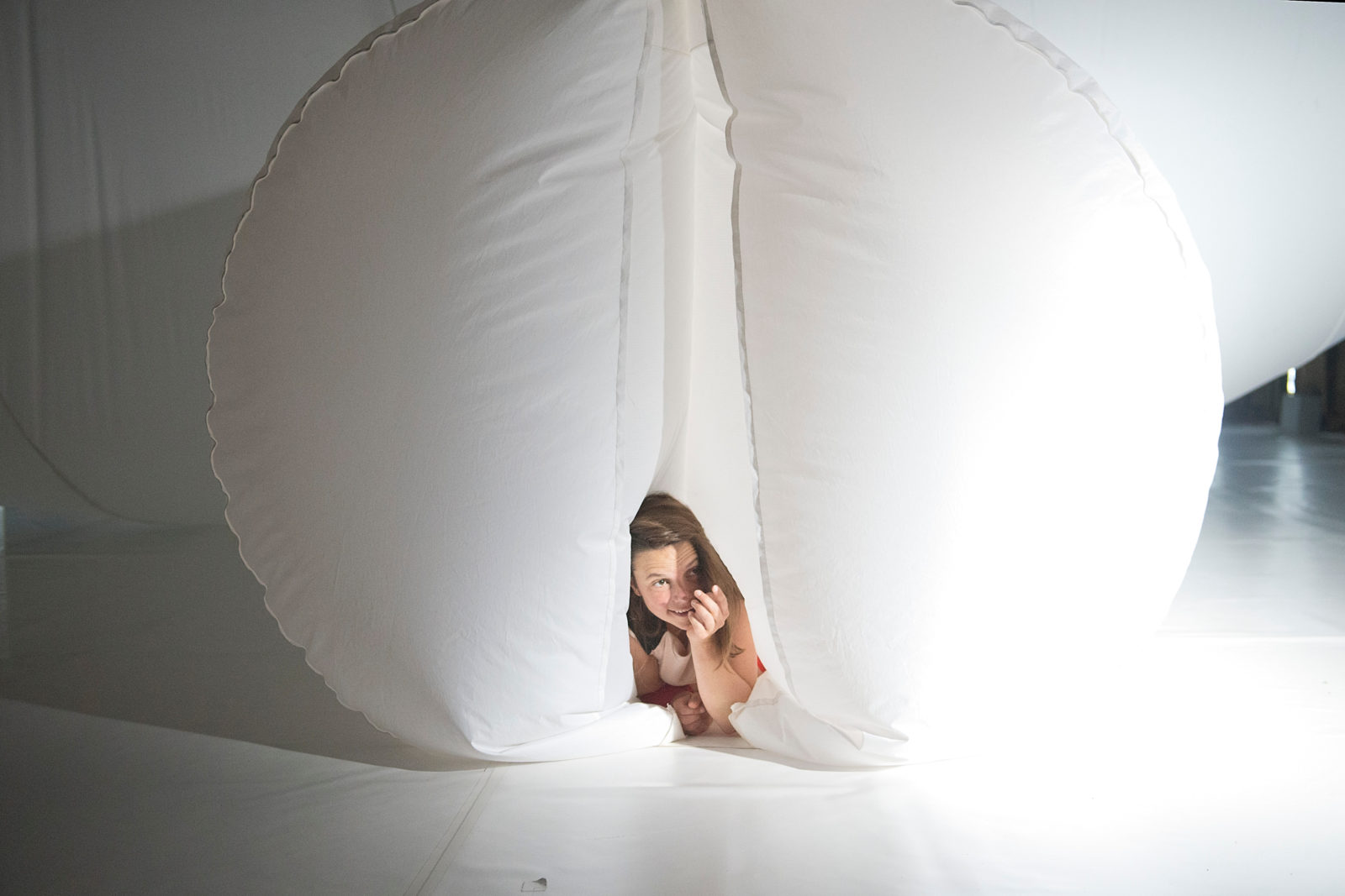 A girl lies smiling on the floor, surround by a giant white blob