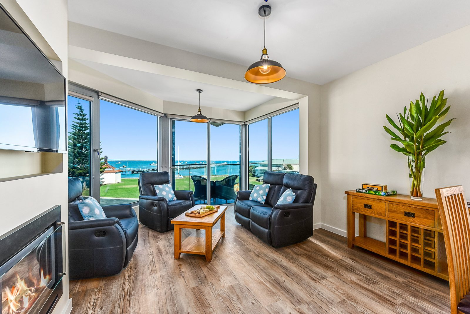 """The living room of """"Cape Martin"""" Apartment 6 with ocean and jetty view, featuring gas log fire place"""