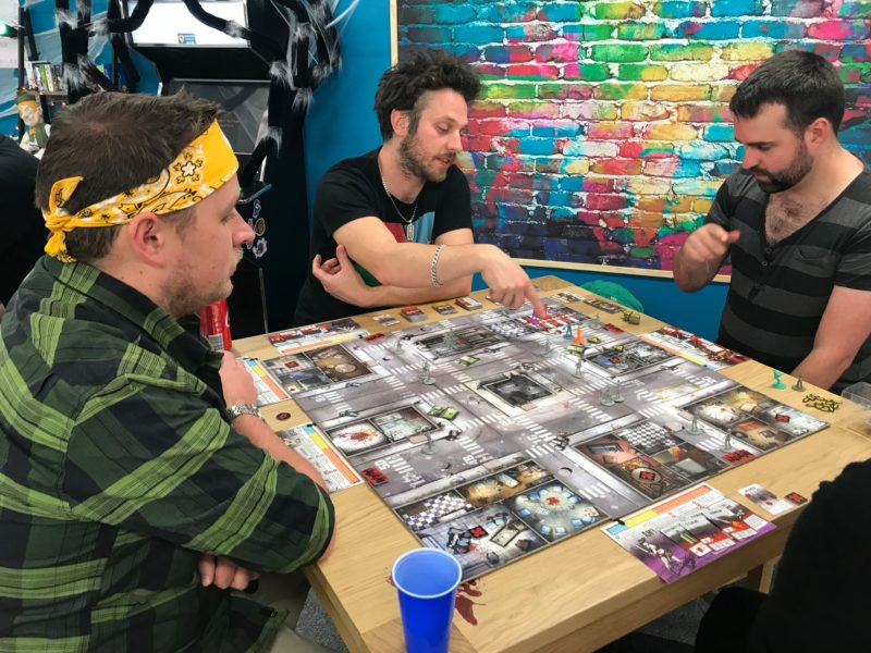 A group discuss strategy while playing Zombicide