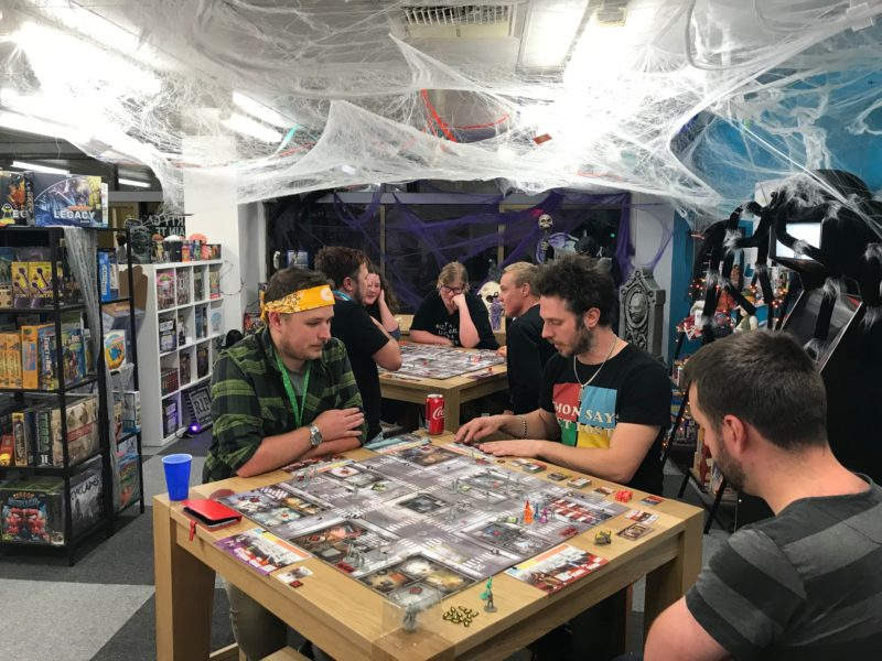 Groups of players gathered around tables in halloween themed room