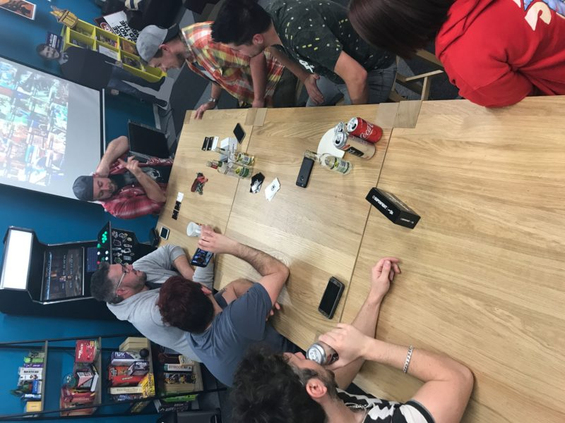 A large group discuss characters in a game of Superfight