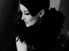 Black and white image of Caroline Nin wearing feather dress