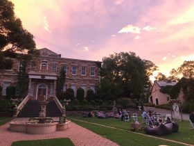 Beautiful pink sunset. Chateau in Bakground. Guests sitting on lawn near fountain.