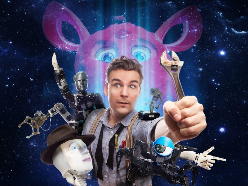 Tech magician Charlie Caper is surrounded by robots from the show under a starry night sky.