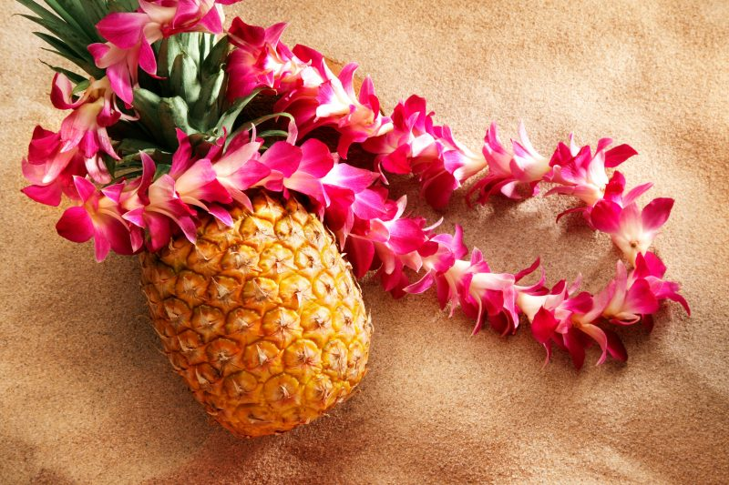 Pineapple and Hawaiian Leis on a beach