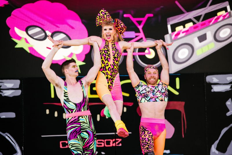 2 white men in fluro leotards lift a white woman by the arms. She also wears a fluro leotard.